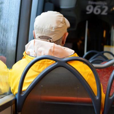 En man i gul regnrock som sitter i en buss med ryggen vänd mot kameran.