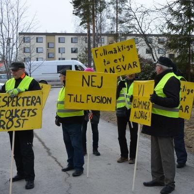 Nio personer står med gula plakat med sloganer mot en kommunsammanslagning.