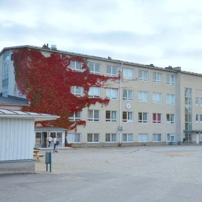 Sarlinska skolas byggnad i halvmulet höstväder. En vit tegelbyggnad med fyra våningar.