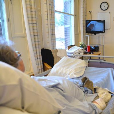 Två äldre som ser på tv i ett rum.