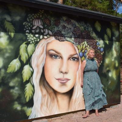 kvinna framför konstverk på husvägg