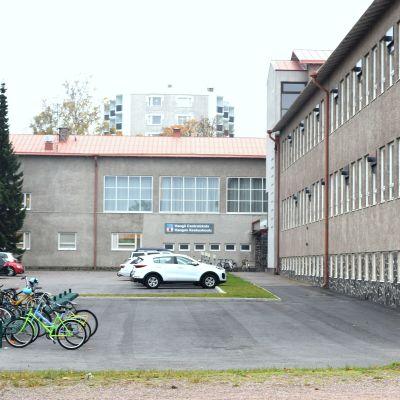 Grå skolbyggnad med parkeringsplats utanför.
