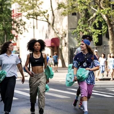 Tre unga tjejer och en ung kille går på en gata i New York bärande på skateboards.