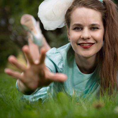Ina Mikkola makoilee nurmikolla.