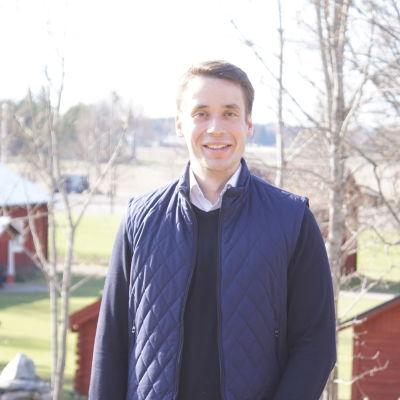 en ung man men börk hår som ler mot kameran, i bakgrunden syns en åker och några röda hus.