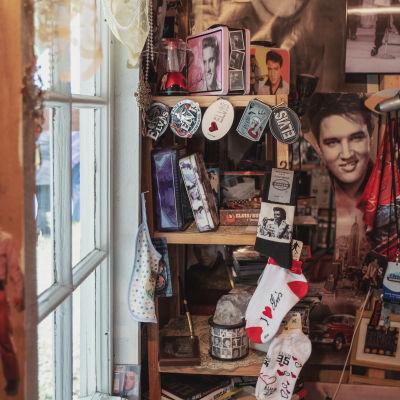 Hylla full med Elvis Presley-saker: strumpor, nyckelringar, askar, foton och böcker.