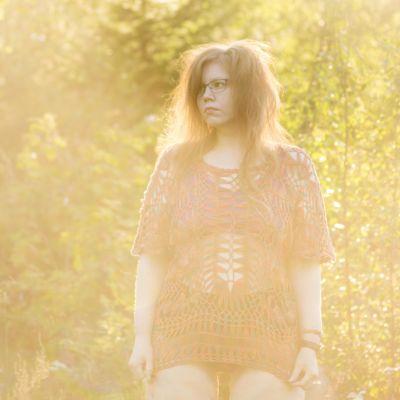 En kvinna iklädd underkläder och ett glesstickat linne. Hon står på en äng och i bakgrunden syns skog. Det är sommar och en dimma sveper in över ängen.