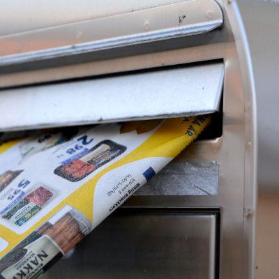 Tidning sticker ut från postlåda