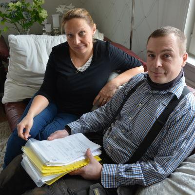 Man och kvinna med pappersbunt i knäet sitter i en soffa.