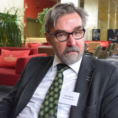 ilpo mKojola på Naturresursinstitutet stirrar stint in i kameran. Han har gråsprängt hår, grått skägg och svartbågade glasögon och är klädd i en grönprickig slips och grå kavaj.