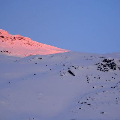 Mitt i bilden syns lavinområdet bakom bergskammen.