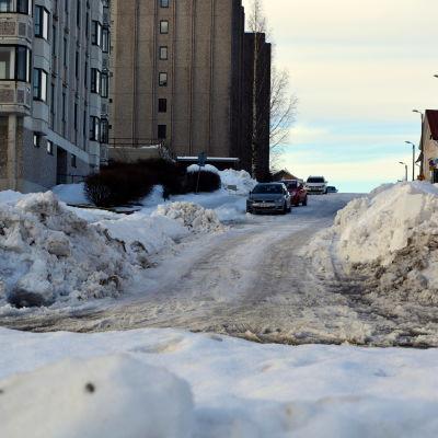 Höga snödrivor längs gata.