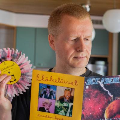 Henrik Gustafsson håller upp den sågtandade vinylsingeln som är en split med Eläkeläiset och Ace Frehley.
