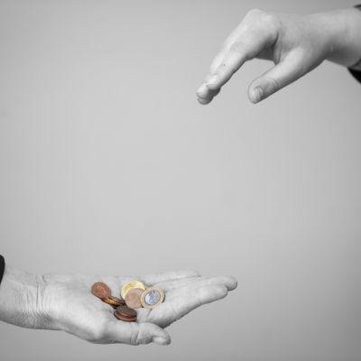 Käsi kurottaa kolikoita kämmeneltä.
