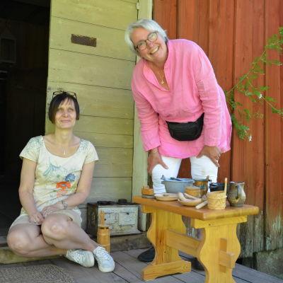 Anne Bergström och Li Näste står på trappan till en röd stuga. Framför dem står ett litet bord med olika kannor och tallrikar på.