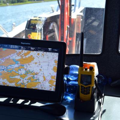 Bilden är tagen från hytten på en båt. Man ser ett digitalt sjökort och en radio framför fönstret.