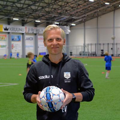 Man står med en fotboll i händerna inne i en fotbollshall.