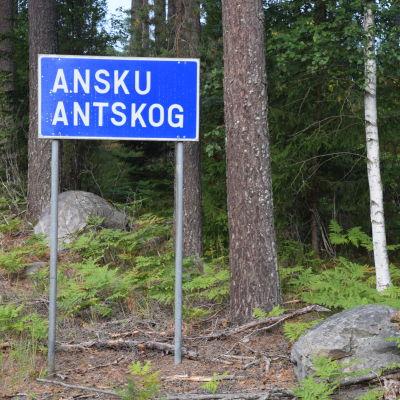 En blåvit trafikskylt längd en vägkant. Det står Ansku Antskog på den.