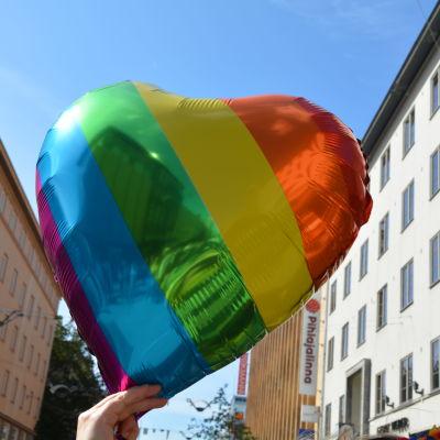 En ballong i form av ett hjärta i regnbågens alla färger.