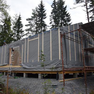 Ett elementhus utvändigt som är nästan klart, bara taket fattas