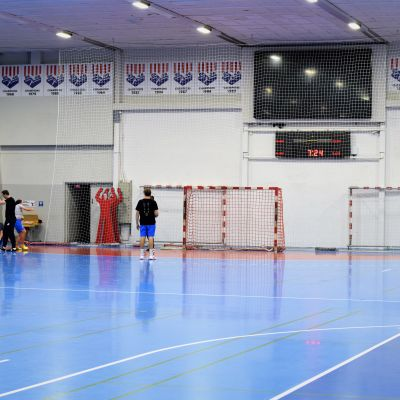 En idrottshall med handbollsspelare som värmer upp.