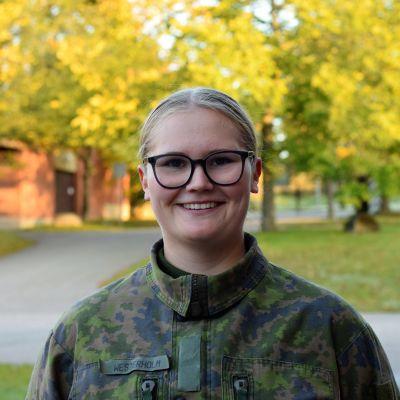 En ung kvinna med militärgrön uniform, i bakgrunden höstlöv.