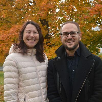 Kvinna i vit jakca och man i glasögon ler mot kameran med höstlöv i bakgrunden.
