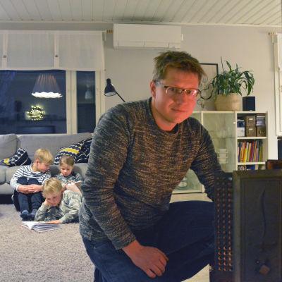 I förgrunden en man som sitter på huk framför kaminen. I bakgrunden tre barn som sitter på golvet och läser.