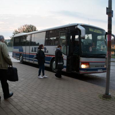 Passagerare stiger på en buss.