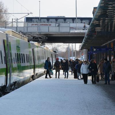 Vasa järnvägsstation, på spåret står ett vitt och grönt VR-tåg. På perongen finns många människor. Det är vinter och det ligger snö på marken.