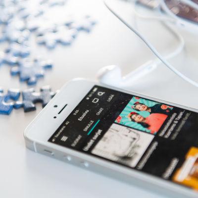En mobilitelefon på bordet där Yle Arenans radiosida syns. På bordet ligger också ett par knapphörlurar och några pussebitar.