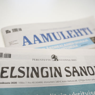 Printversionerna av tidningarna Helsingin Sanomat och Aamulehti på varandra på en vit yta.