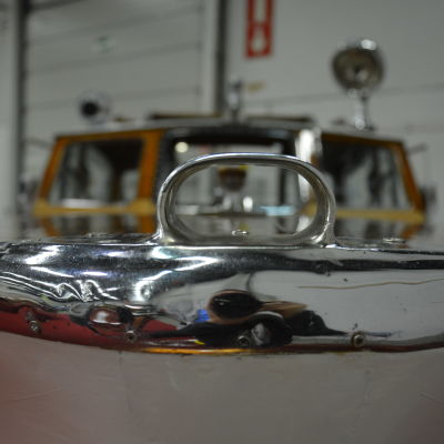 Fören på en gammal träbåt glänser i ljus metall.