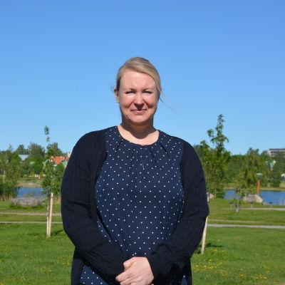 Tatjana Asplund står i en park. I bakgrunden syns vatten och höghus bland träden.