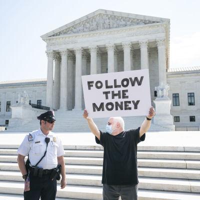 Mies kädessään kyltti, jossa lukee Follow the Money. Vieressä poliisi.