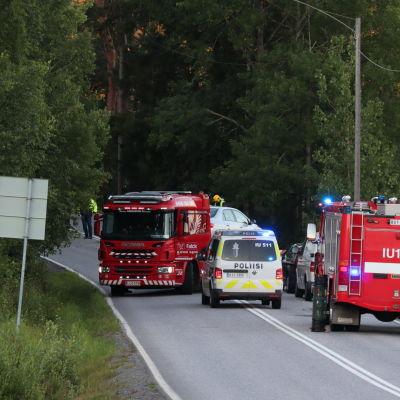 Två stora röda brandbilar och en huvudsakligen vit polisbil på en smal väg omgiven av träd och en åker.  Brandkåren och polisen på olycksplatsen i Borgå.