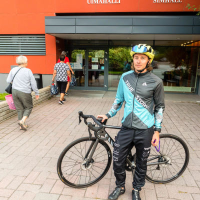 En man med cykel som står framför simhallen.