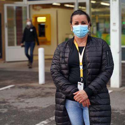 En kvinna som står utomhus med ett munskydd på sig.