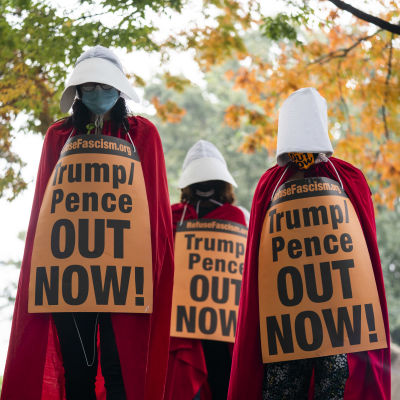 Kolme orjattaren asuun pukeutunutta mielenosoittajaa kaulassaan Trumpia ja Penceä vastustavat kyltit.