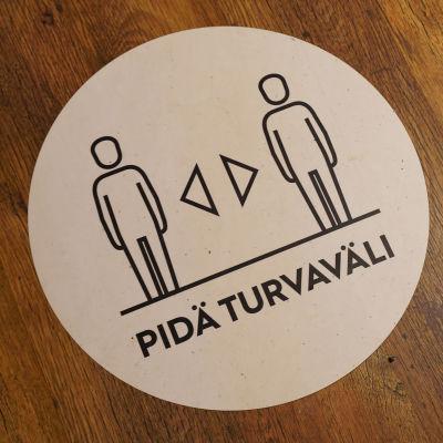 Ett klistermärke på ett golv som påminner om att man ska hålla säkerhetsavstånd.
