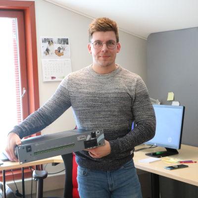En man i glasögon håller i en apparat.