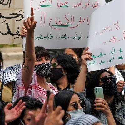 Azza Slimene käsi kohotettuna mielenosoittajien keskellä.