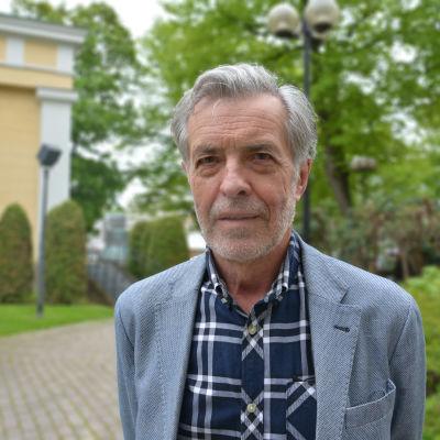 En man med rutig skjorta och grått hår.