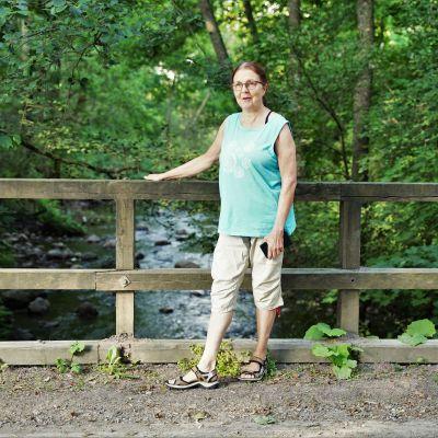 Agneta Ekbom står på en bro och håller i träräcket.