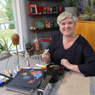 Camilla sitter vide ett bord med en ukulele och färglada pennor.