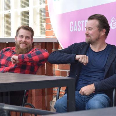 Köttkontrollens restaurangchef Mikael Kokkonen gör den såkallade coronahälsningen med affäremannen Olli Muurainen på Köttkontrollens terass. Två män rör vid varandras armbåge, sittande framför en tegelvägg.