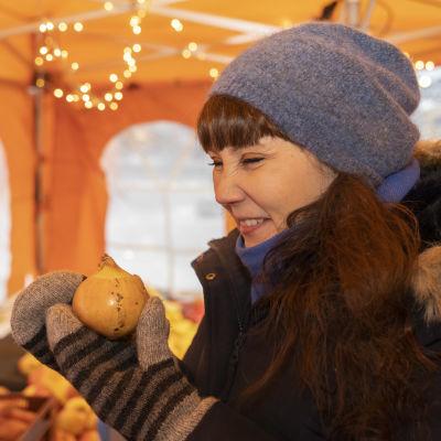 Koronan sairastanut Johanna Pekari Kauppatorilla torikojussa haistelee sipulia
