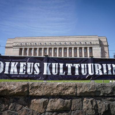 """Kulttuurialan mielenilmaus Eduskuntatalon ja Oodin välissä. Kuvassa banderolli jossa lukee """"oikeus kulttuuriin""""."""