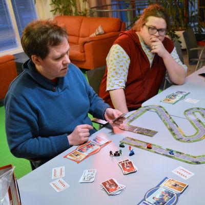 Personer spelar brädspel kring ett långbord.