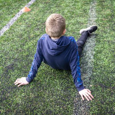 Poika istuu urheilukentällä.
